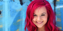 Smiling, young and pretty woman with pink hair on a blue background