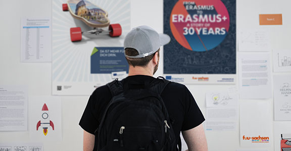 young man stands in front of an information board about EU projects