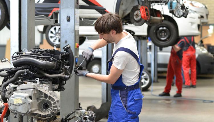 Automotive mechatronics technician works in a car repair shop