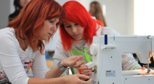 Instructor shows a student the handling of a sewing machine