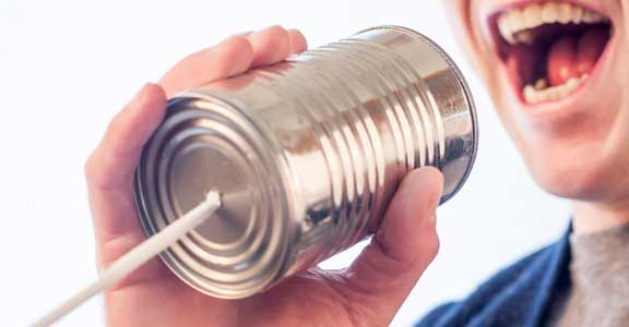 Teenager with tin can telephone