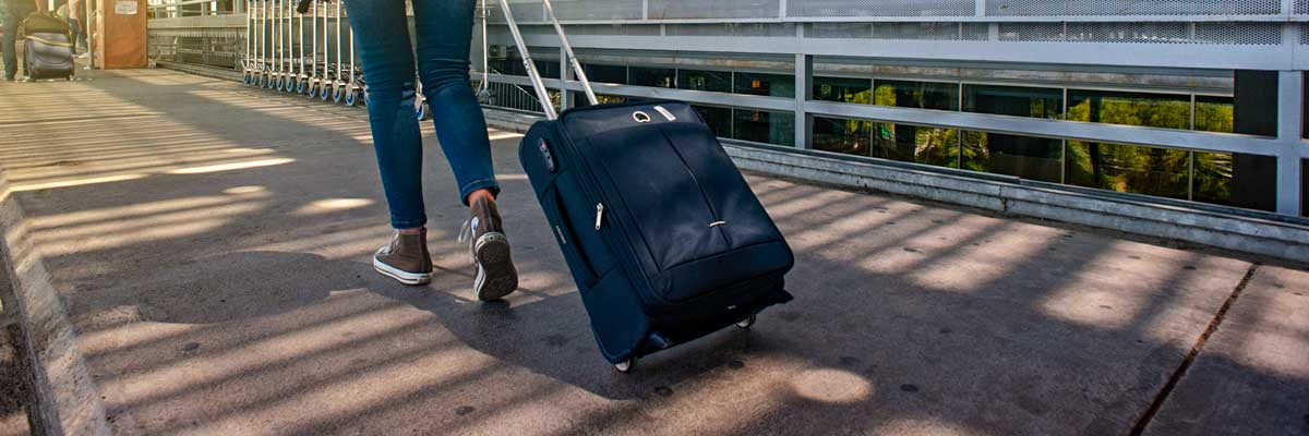 Airport arrival - Woman walking on pathway with luggage