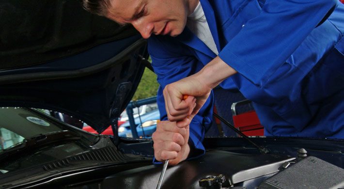 Automotive mechatronics technician repairing a car