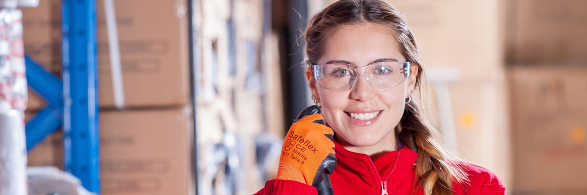 Young woman with safety glasses and safety gloves in a warehouse