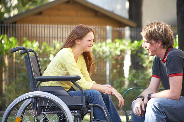 a girl in a wheelchair talking to a boy in the park