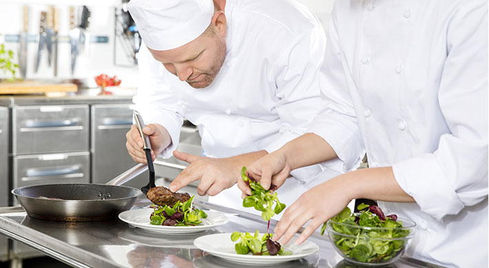 two chefs preparing meals