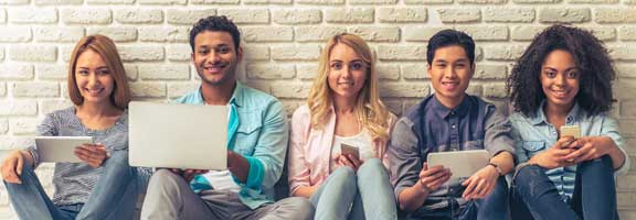 Young people of different nationalities smiling, sitting against white brick wall