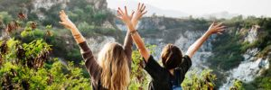 Two girls on a mountain stretch their hands in the air