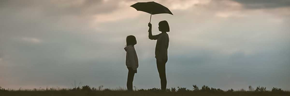 silhouette of woman holding umbrella standing in front of girl on hill